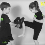 young girl kicking training pads with you boy helping